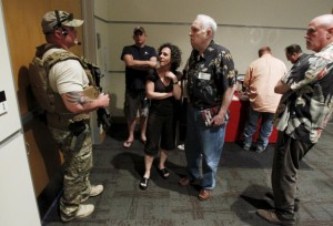 A police officer prevents attendees from leaving the Muhammad Art Exhibit and Contest after shots were fired outside the venue in Garland, Texas