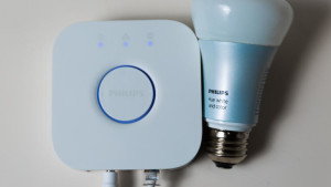 A Philips Hue bulb, pictured alongside a second generation Philips Hue bridge.