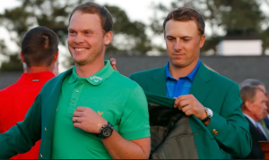 A disappointed Jordan Spieth presents Danny Willett with the green jacket