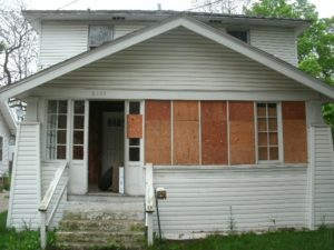 An all too common sight, this home has been boarded and put up for sale.