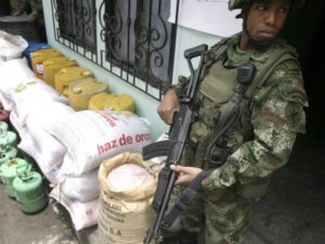 A colombian soldier standing guard in confiscated explosive supplies in Palmira.
