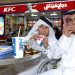 Qatari children in traditional outfits eating fast food in a Doha shopping mall.. Image shot 11/2005. Exact date unknown.