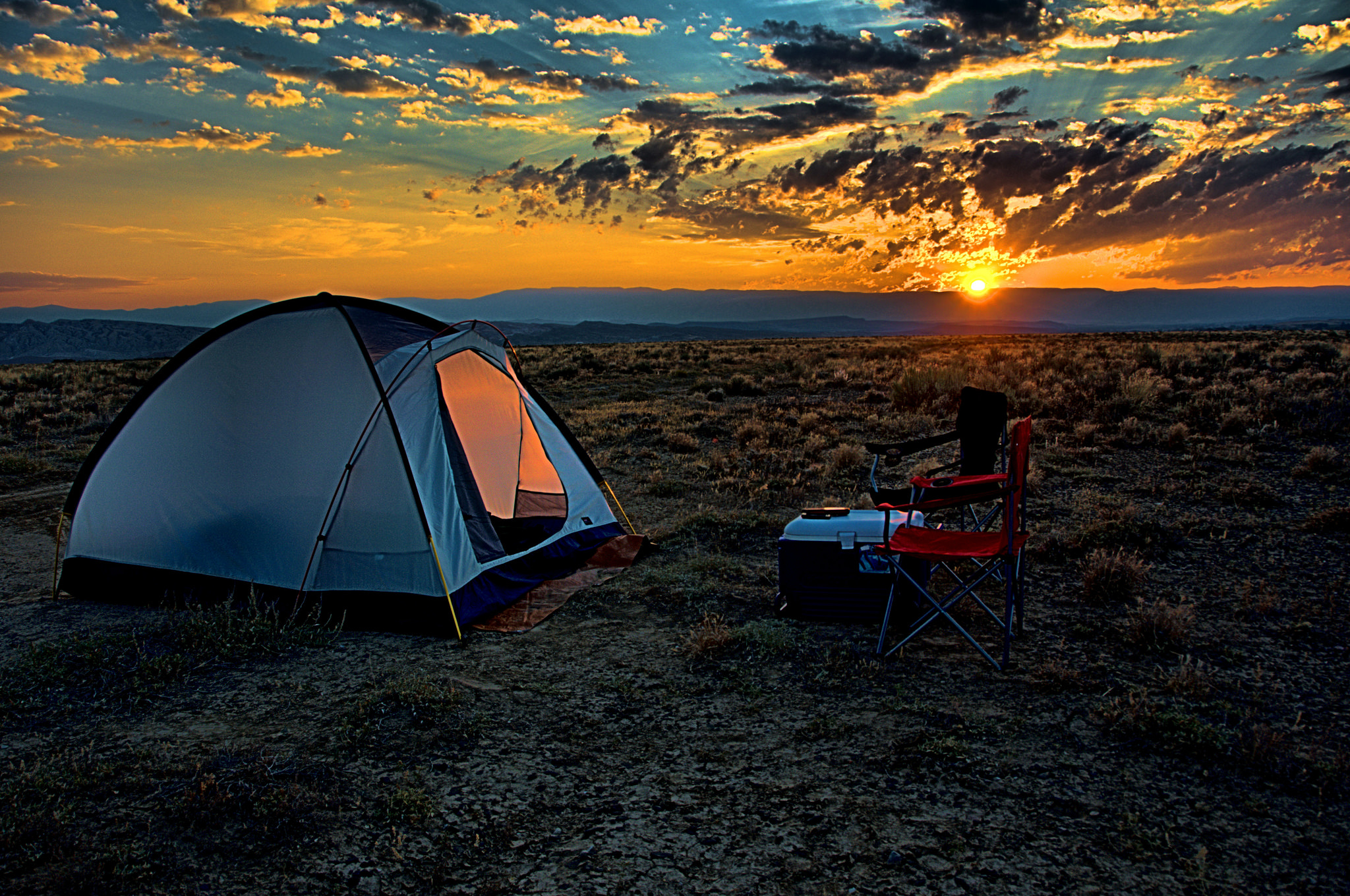Camping chair and tent on a plain at sunset