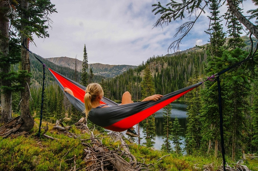 A young woman in a hammock overlooking mountains