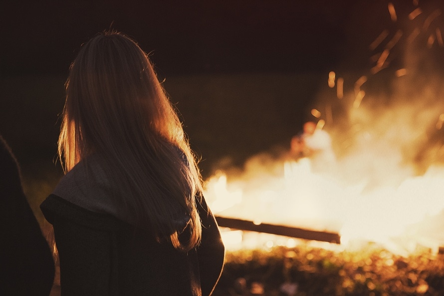 A woman standing in front of a fire - camping stoves
