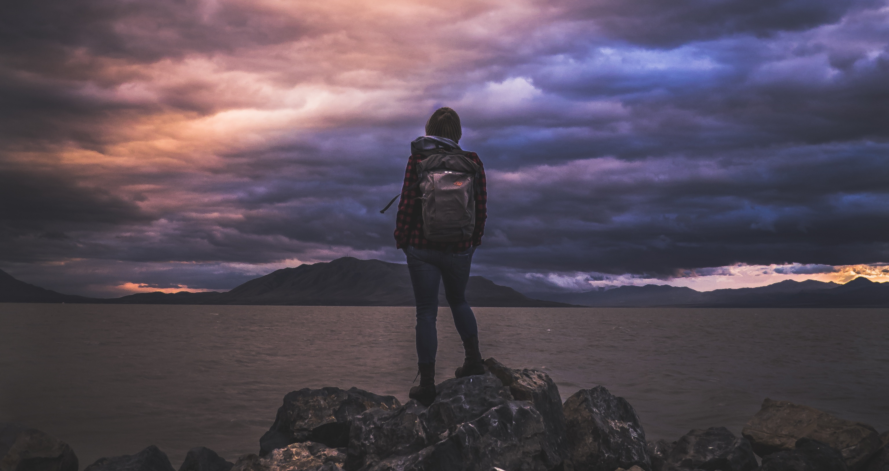 Figure wearing a backpack standing on rocks in front of a lake with a dramatic, cloudy sky